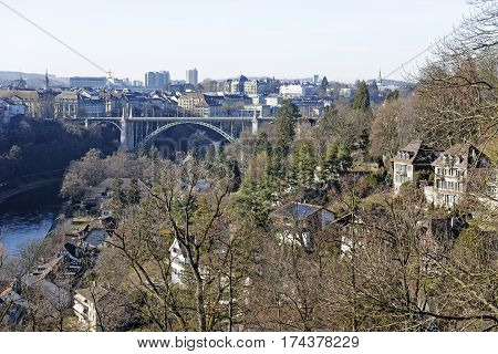 BERN SWITZERLAND - DECEMBER 26 2015: Vegetation enriches the landscape of the city. High bridge spanning the river Aare and the dense urbanization can be seen