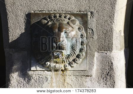 LUCERNE SWITZERLAND - MAY 05 2016: View of an ancient fountain which is placed on a pillar that is a part of arcades of one of the buildings in the old town