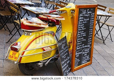 Nice France - May 18 2014: Vespa scooter parked on a sidewalk next to the outdoor seating restaurant is used as a stand to showcase the current menus
