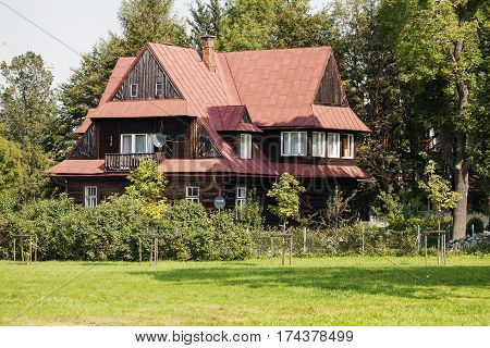 ZAKOPANE POLAND - SEPTEMBER 13 2016: Wooden dwelling house that probably was built in 1920. This building is surrounded with lots of shrubs and trees