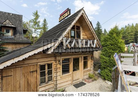 ZAKOPANE POLAND - SEPTEMBER 12 2016: Wooden building architecture is reminiscent of the style of the region. Large lettering defines the use of the building this is regional restaurant