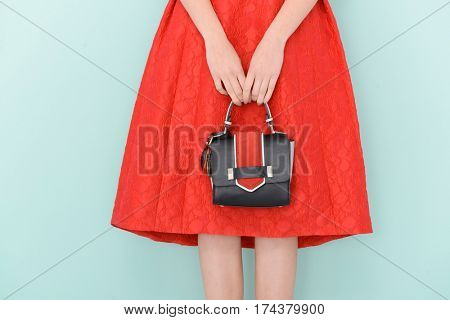 Woman in stylish red sundress . Perfect female sexy long legs holding handbag-light blue background