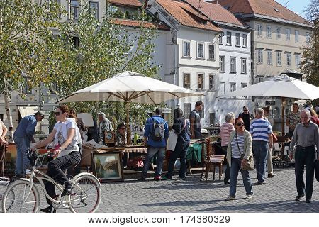 LJUBLJANA SLOVENIA - OCTOBER 12: People at Antique Market in Ljubljana on OCTOBER 12 2014. Shoppers at New Square Sunday Market in Ljubljana Slovenia.