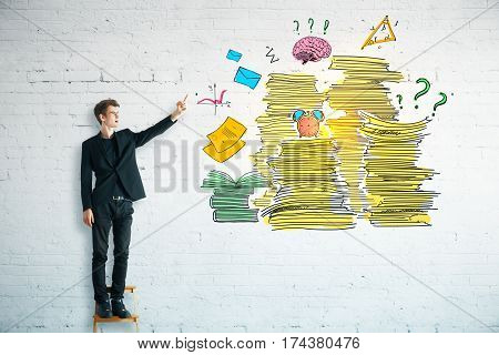 Young businessman with drawn paperwork pile on brick wall. Workload concept