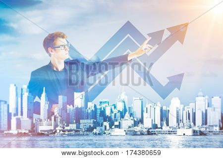 Young businessman on abstract waterfront city background pointing at upward business chart arrows sketch. Financial growth concept. Double exposure