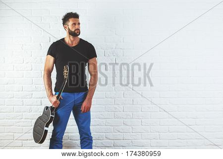 Portrait of handsome caucasian man with electric guitar in hand standing on white brick background with copy space