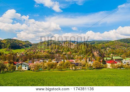 Rural landscape with lush green meadow, blue sky and white clouds at Mala Skala in Bohemian Paradise, Czech Republic.