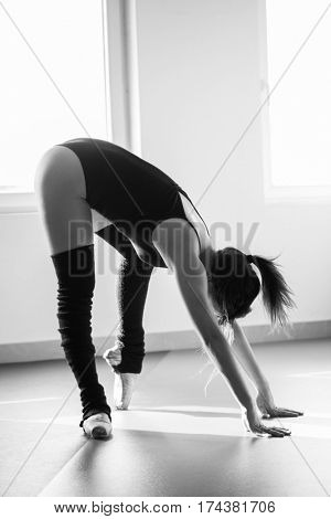 young dancer woman doing stretching on ballet class indoor shot in bw
