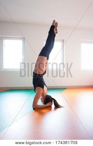 young ballet dancer practice stand on head indoor shot