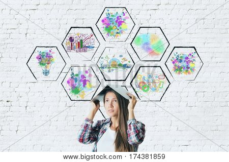 Worried young woman covering head with book on brick background with abstract colorful drawings inside cells. Creativity concept