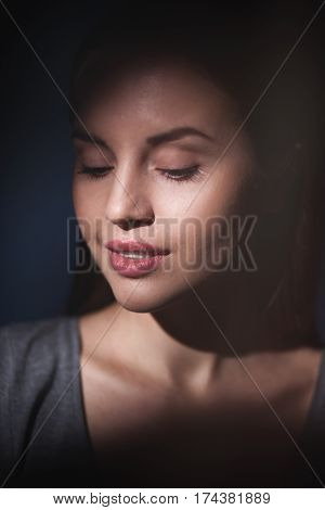 closeup portrait of young woman with clean fresh skin and closed eyes. Dramatic studio portrait.