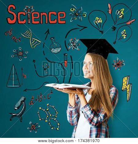 Attractive cheerful young caucasian woman with open book drawn mortarboard and other education related drawings. Graduation concept