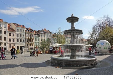 LJUBLJANA SLOVENIA - OCTOBER 12: People Walking Near Fountain at New Square in Ljubljana on OCTOBER 12 2014. Pedestrians at Novi Trg in Ljubljana Slovenia.
