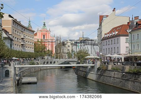 LJUBLJANA SLOVENIA - OCTOBER 12: Downtown Ljubljana on OCTOBER 12 2014. The Triple Bridge over the Ljubljanica River in the city center in Ljubljana Slovenia.