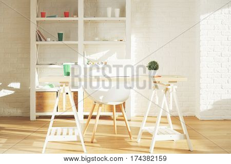 Contemporary office interior with items on shelves laptop on table other items equipment and sunlight