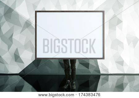 Businessman covering himself with empty picture frame in clean interior with polygonal wall and shiny floor. Mock up 3D Rendering