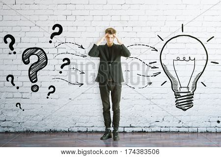Thoughtful man with drawn question marks and lamp on brick background. Idea concept