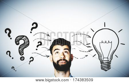 Pensive man with drawn question marks and lamp on grey background. Idea concept