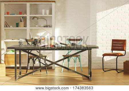 Creative office interior with items on shelves laptop on table other items equipment and sunlight