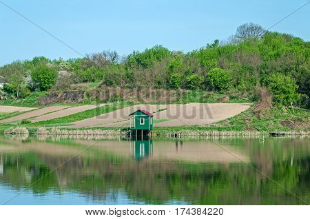 Small fishing hut on the rural shore of pond in early spring