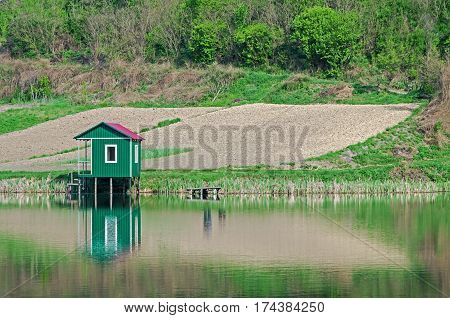 Small fishing lodge on the rural shore of pond in early spring