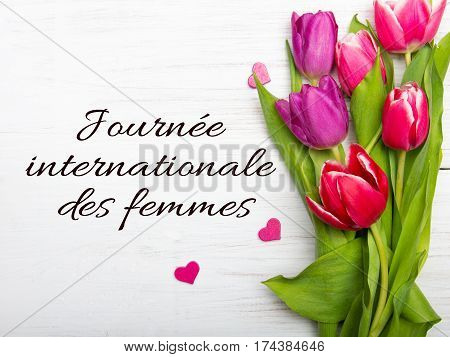 Womens day card with French words 'Journée internationale des femmes'. Tulip bouquet on white wooden background
