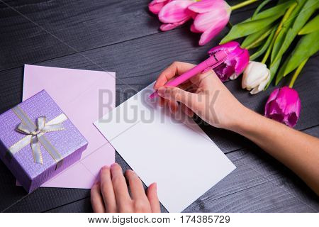 Female Hands Writing On Clear Paper With Gift Box And Bouquet Of Tulips