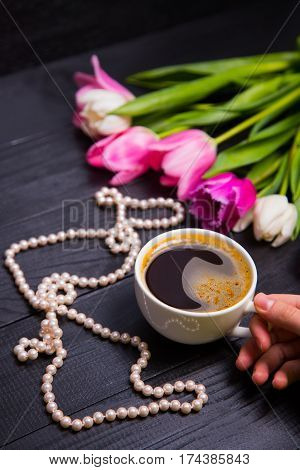 Bouquet Of Tender Pink Tulips And Hands Holding Cup Of Coffee And Pearls On Black Wooden Background