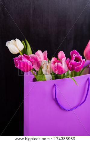 Bouquet Of Tender Pink Tulips In Purple Shopping Bag On Black Wooden Background