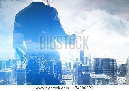 Rear view of a businessman holding his smartphone and looking at its screen. There is a cityscape in the background. Toned image. Double exposure. Film effect