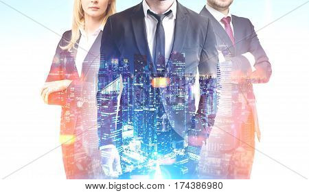 Business trio in a night city. Close up of two businessmen and a businesswoman standing together against a cityscape. 3d rendering double exposure toned image