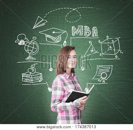 Portrait of a geek girl holding a black book and standing near a green chalkboard with an MBA sketch on it.