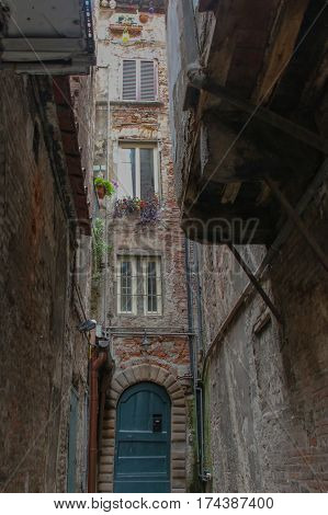 Italy Lucca - September 18 2016: the view of narrow street and dilapidated building in Lucca on September 18 2016 in Lucca Tuscany Italy.