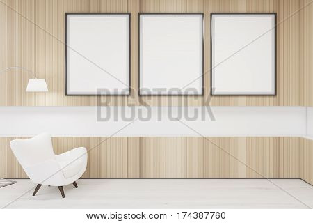 Poster gallery with framed empty pictures hanging on a wooden wall. There is a white armchair and a floor lamp standing beside it. 3d rendering mock up