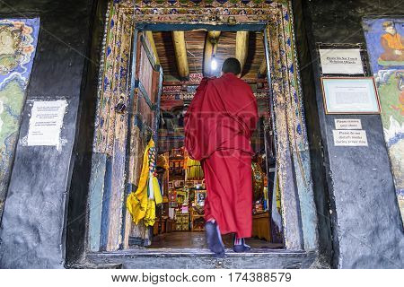 Thiksey, India - August 24, 2015: A buddhist monk entering in the prayer hall of Thiksey monastery for the Puja, a prayer ritual performed by Hindus and buddhist for worship one or more deities