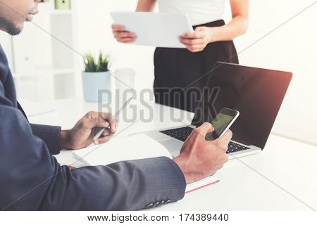 Young African Man With Cell Phone In Office