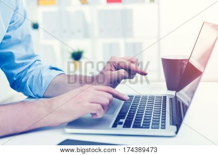 Close up of a man wearing a blue shirt. He is typing at his laptop keyboard with two fingers. Toned image.