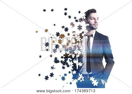 Portrait of young bearded businessman wearing a gray suit and a tie and standing against a white background. He is made of puzzle pieces