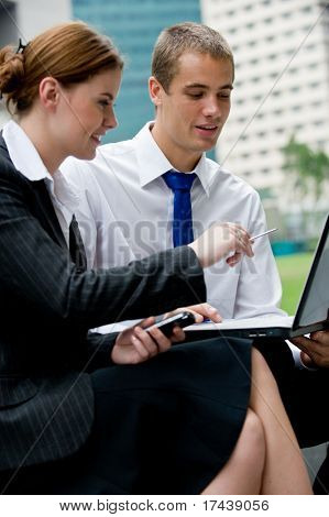 Two young business professionals sitting outside with a laptop computer