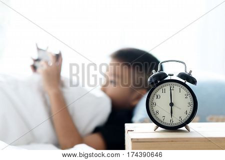 Focus On Alarm Clock And Asian Boy Using Cellphone.