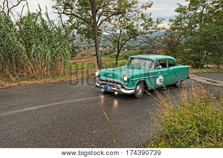 MELDOLA FC ITALY - SEPTEMBER 18: driver and co-driver on a vintage American car Oldsmobile Super Rocket 88 (1954) in classic car rally