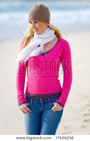 A young attractive woman walking along a sandy beach in autumn