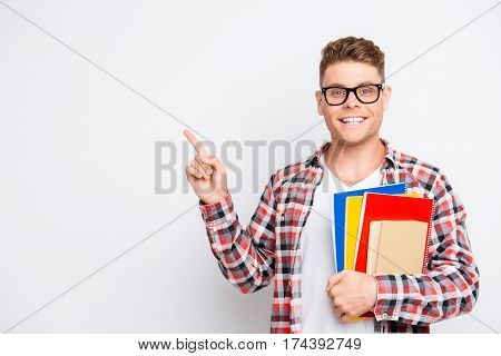 Cheerful Student Holding Educational Materials And Pointing On A Copy Space