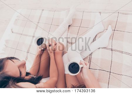 Top View Of Two Girls Sitting On Bed With Cups Of Coffee In Hands