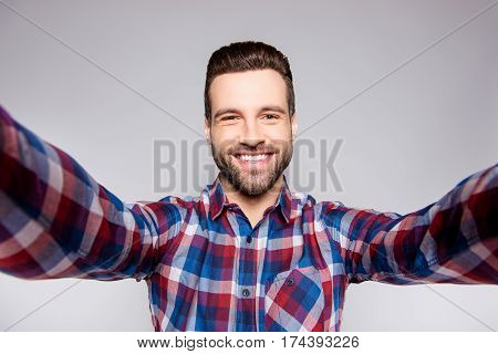 Young Satisfied Cheerful Man Smiling And Taking A Selfie Against Gray Background