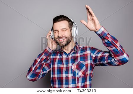 Handsome Guy In Headphones Enjoying Music And Waving His Hand