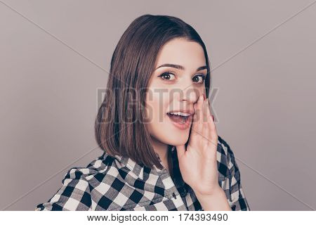 Young Woman In Checkered Shirt Holding Hand Near Mouth And Telling A Secret
