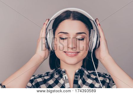 Portrait Of Young Nice-looking Woman In Headphones With Closed Eyes Listening To Music
