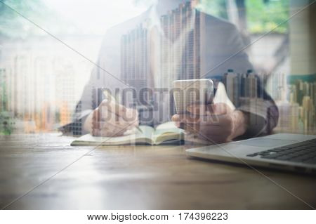 Double exposure photo. Business man using smartphone laptop and note data to notebook with City many building background