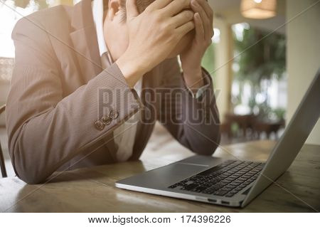 Frustrated middle aged businessman sitting at office desk